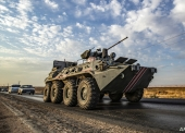 A Russian military police armoured personnel carrier (APC) drives along a road in the countryside near the northeastern Syrian town of Amuda in Hasakeh province on October 24, 2019, as part of a joint patrol between Russian forces and Syrian Kurdish Asayish internal security forces near the border with Turkey. - Russian forces have started patrols along the flashpoint frontier, filling the vacuum left by a US troop withdrawal that effectively returned a third of the country to the Moscow-backed regime of President Bashar al-Assad. (Photo by Delil SOULEIMAN / AFP)